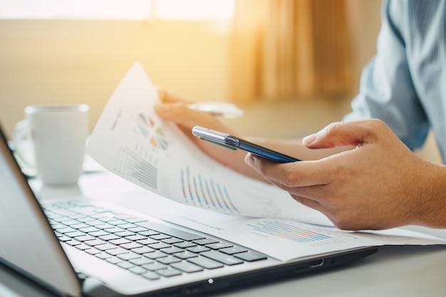 Бизнесмен работая дома офис с умным телефоном и портативным компьютером.