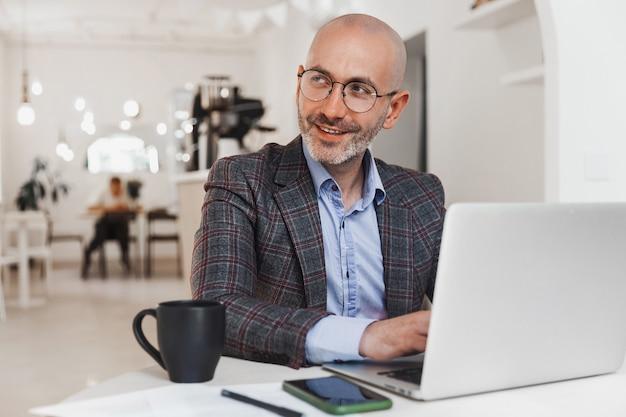 ノートパソコンで働くビジネスマンは笑顔で横を向いています