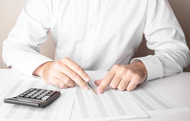 Бизнесмен, работающий за столом с ручкой и калькулятором на белом фоне.