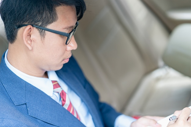 Businessman working in the backseat of a car