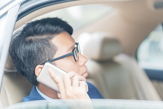 Businessman working in backseat of a car