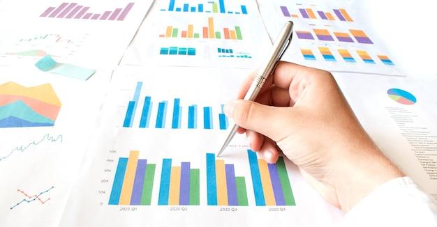 Бизнесмен работает рассчитать документ данных график диаграмма отчет разработка маркетинговых исследований