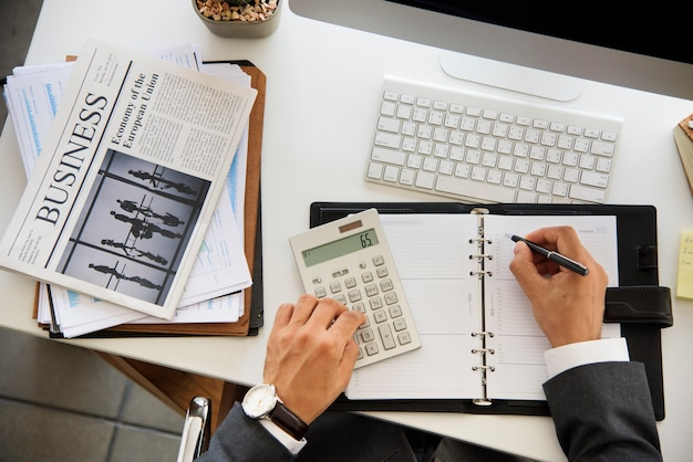 Бизнесмен работает рассчитать написание белый стол