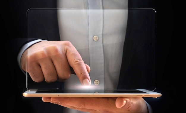 Businessman working from his tablet with digital virtual screen