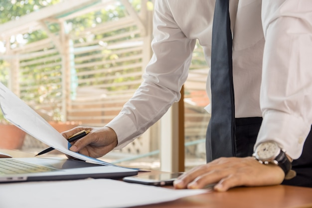 Businessman working at his office with documents paperwork.