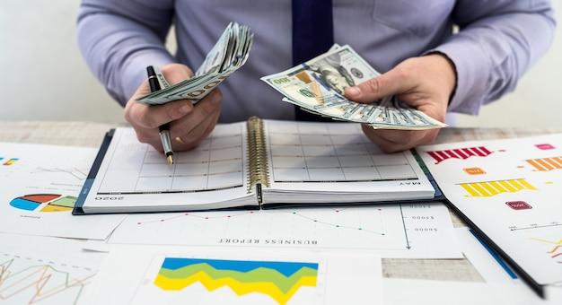 オフィスで働くビジネスマン。男性は商品のレンタルまたは販売からの利益を数えます。事業分析と戦略の概念。テーブルにドルが記載されたビジネスグラフとドキュメント。