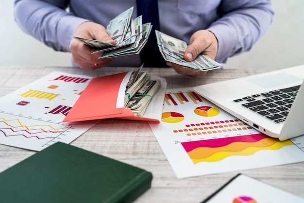 オフィスで働くビジネスマン。男性は商品のレンタルまたは販売からの利益を数えます。ビジネス分析と戦略の概念。