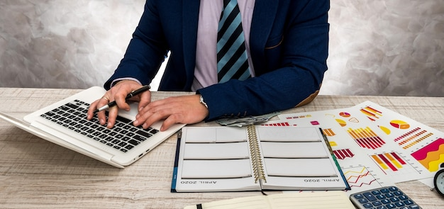 ビジネス グラフ、ラップトップ、メモ帳を使ってオフィスで働くビジネスマン。