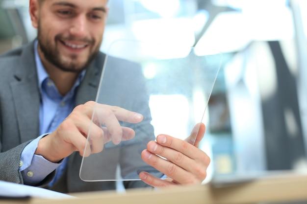 투명한 태블릿과 노트북으로 사무실에서 일하는 사업가입니다.