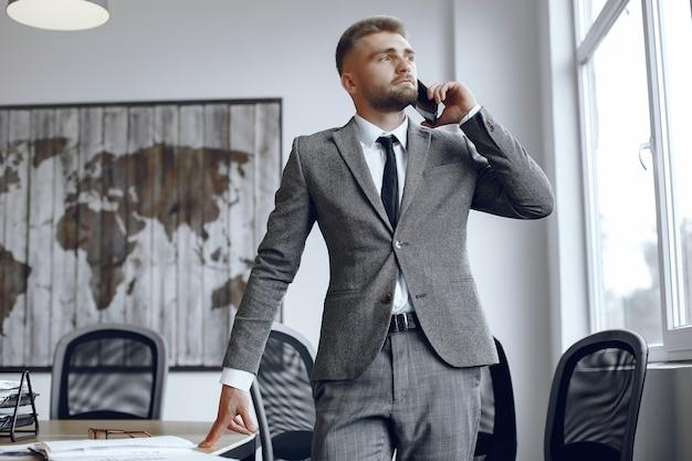 Бизнесмен, работающий в офисе. человек разговаривает по телефону. парень в деловом костюме