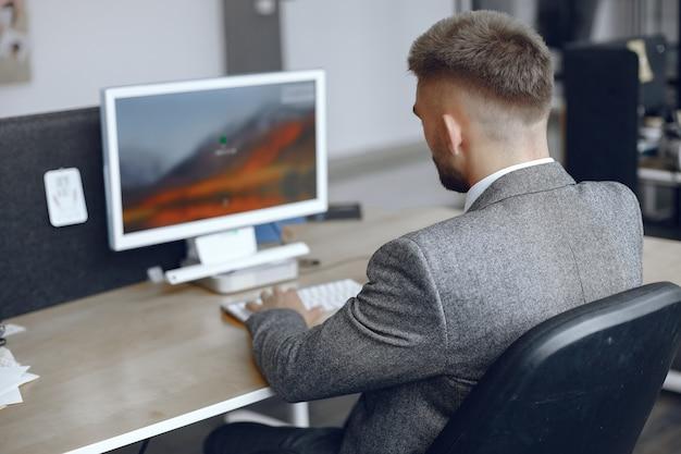 Бизнесмен, работающий в офисе. человек использует компьютер. парень сидит в офисе