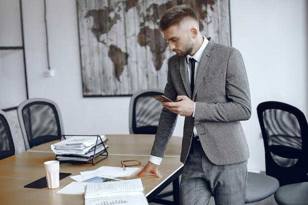Бизнесмен, работающий в офисе. человек использует телефон. парень в деловом костюме