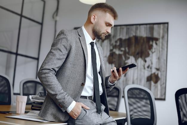 Бизнесмен, работающий в офисе. человек использует телефон. парень сидит в офисе