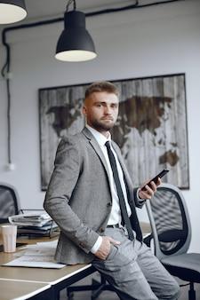 사무실에서 일하는 사업가. 남자는 전화를 사용합니다. 남자는 사무실에 앉아