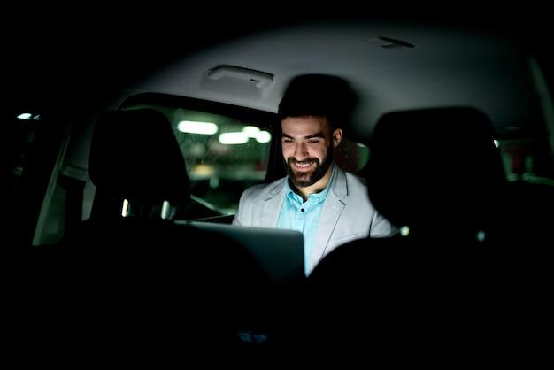 Бизнесмен, работающий поздно в машине, заканчивая свою работу. тяжелая сверхурочная работа по дороге домой.