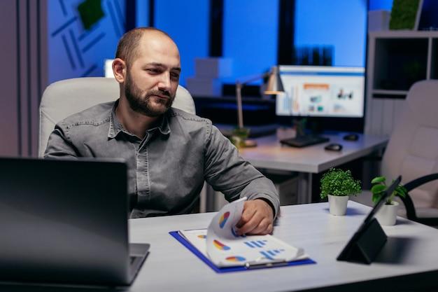 Бизнесмен, работающий поздно ночью на рабочем месте, используя планшетный пк, держа руку на буфере обмена с диаграммой. бородатый предприниматель вечером осматривает офис, чтобы закончить срок.