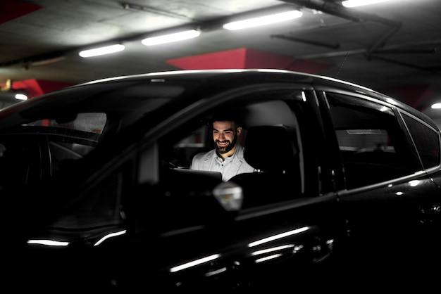 ガレージで車に座って遅くまで働くビジネスマン。ラップトップフリーランサー働く男。