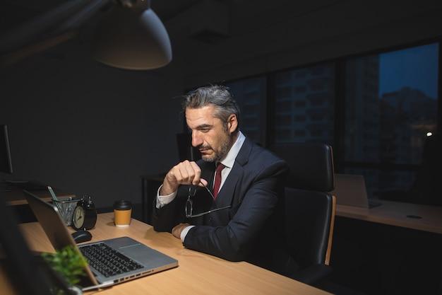 Бизнесмен работает поздно, сидя на столе в офисе ночью