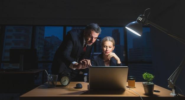 밤에 사무실에서 비서와 책상에 앉아 늦게까지 일하는 사업가