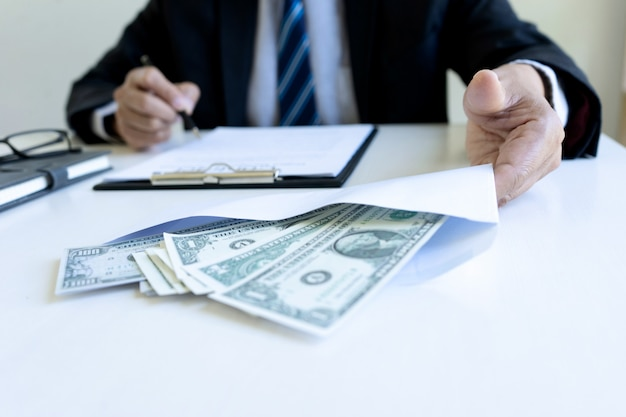 Businessman working at office desk with money