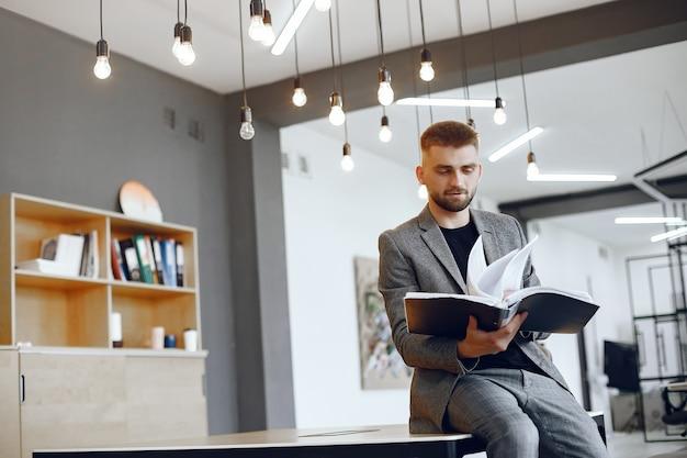 Uomo d'affari che lavora in ufficio.l'uomo tiene una cartella. guy è seduto in ufficio