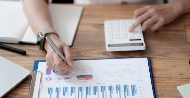 デスクオフィスビジネス財務会計計算、グラフ分析に取り組んでいるビジネスマン