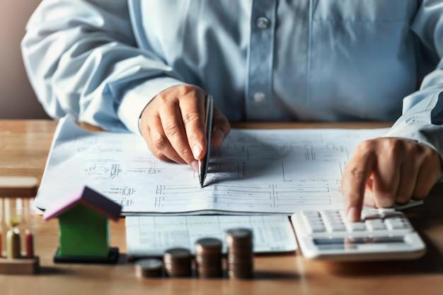 電卓を使用して財務会計の概念を計算するデスクオフィスで働くビジネスマン