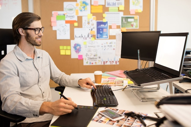 Бизнесмен, работающий над дигитайзером на творческом офисном столе