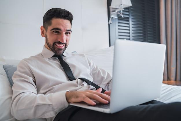 호텔 방에서 자신의 노트북에서 일하는 사업가.