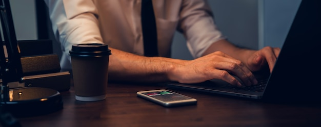 Бизнесмен, работающий на ноутбуке и анализ графиков на экране линии свечи на смартфоне в офисе в ночное время.