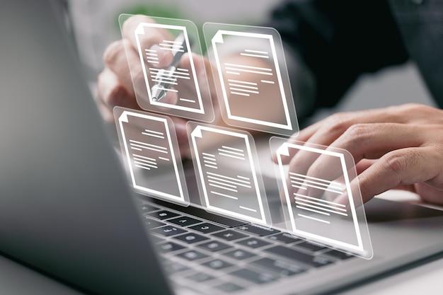 Бизнесмен, работающий на портативном компьютере с электронными значками документа управление документами