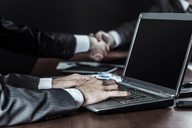 Бизнесмен, работающий на ноутбуке на фоне рукопожатия деловых партнеров.