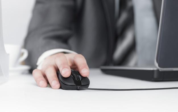 彼の机に座って、ラップトップに取り組んでいるビジネスマン