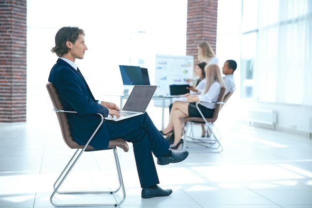 会議室に座ってラップトップに取り組んでいるビジネスマン。