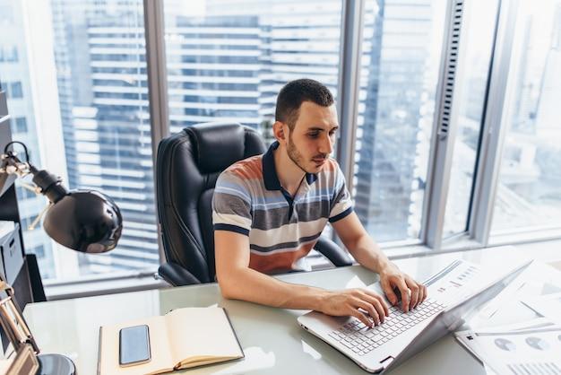 Бизнесмен, работающий на ноутбуке, используя интернет для поиска информации, сидя за столом в офисе.