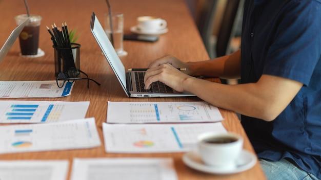 Бизнесмен, работающий на ноутбуке с финансовым отчетом, канцелярскими принадлежностями, чашкой кофе на деревянном столе
