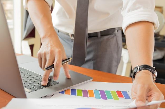 Бизнесмен работая на компьтер-книжке при руки держа отчет с анализировать диаграмму.