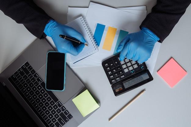 사무실 책상에서 일하는 사업가. 노트북과 계산기를 사용하여 메모 작성하기