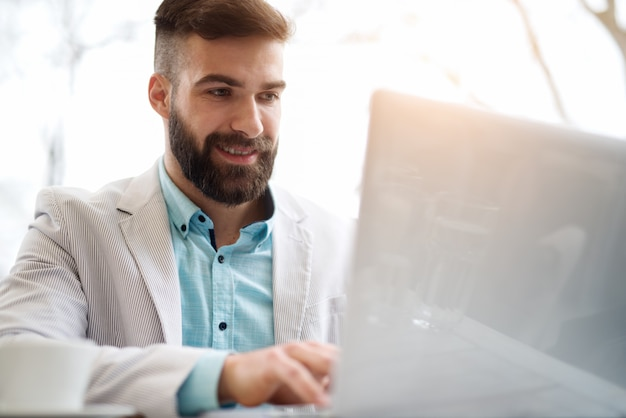 ネットサーフィンインターネットショッピングをサーフィンのオフィスの外で働くビジネスマン。