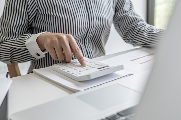 Businessman working in a private office, she is reviewing the company's financial documents sent from the finance department before he takes it to a meeting with a business partner. financial concept.