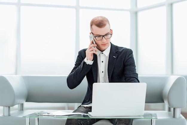 Бизнесмен, работающий, сидя в холле бизнес-центра