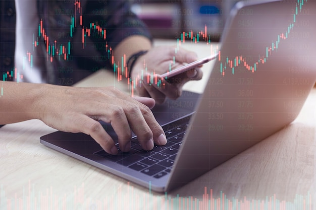 デジタル市場と投資の分析を行うビジネスマンのワーキングストックトレーダー