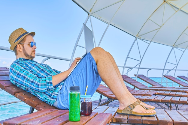 Businessman working summer beach. man in shorts, shirt, sunglasses and hat with laptop