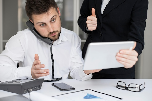 Бизнесмен, работая вместе в офисе