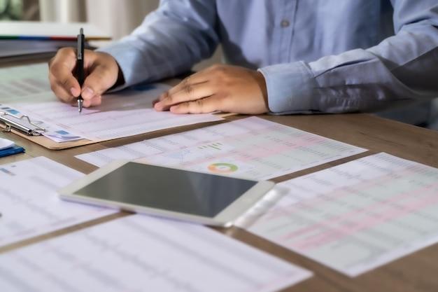 電卓ファイナンス会計概念達成を使用して働いているビジネスマン男性アシスタント会計のバランスをとる