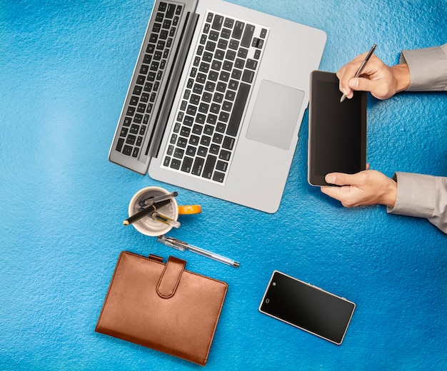 Businessman working using digital tablet, laptop, mobile phone on office desk