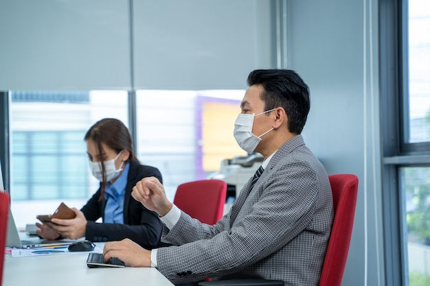 Businessman working and wear mask for protect covid-19 or corona virus disease at modern office.