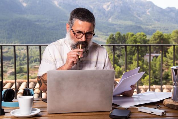 屋外で彼の家のバルコニーでラップトップを使用して作業しているビジネスマン。在宅勤務の概念