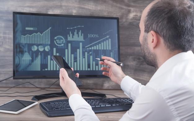 Бизнесмен, работающий с аналитикой, сидя на рабочем месте с компьютером. графики и диаграммы на экране компьютера. бизнес. финансы. бухгалтерия