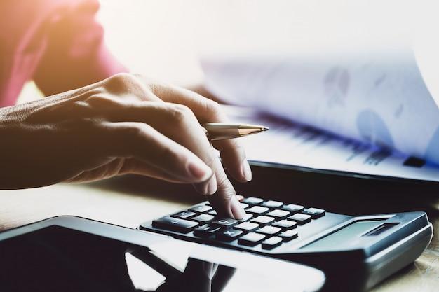 ビジネスマンのオフィス、簿記係および監査人の概念で財務ビジネス戦略レイヤー効果を持つ電卓とデジタルタブレットの操作。